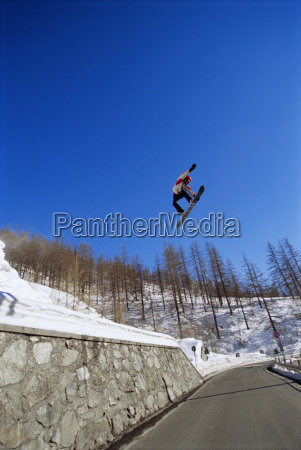 snowboarder doing jump on snowy hill