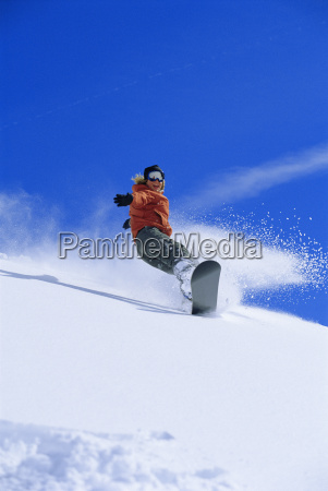 snowboarder coming down snowy hill smiling