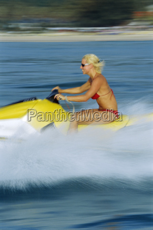 woman jet skiing and smiling blur