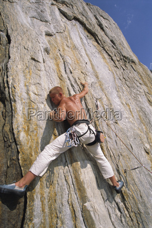 free climber scaling cliff face