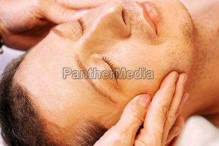 man gets facial massage reiki