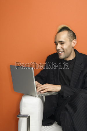 businessman with mohawk on laptop
