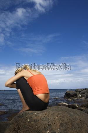 woman sitting on rocky shore