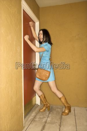 woman pounding at door