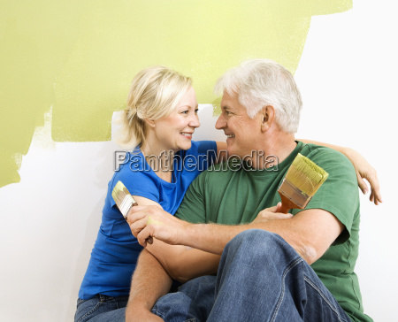 man and woman snuggling while painting