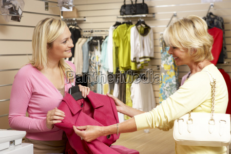 sales assistant with customer in clothing