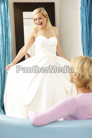 bride trying on wedding dress with