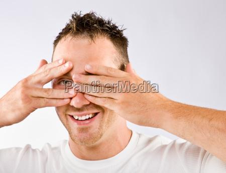 man peering from behind hands