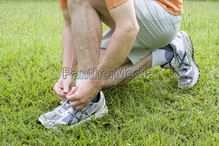 man binds running shoes on grass