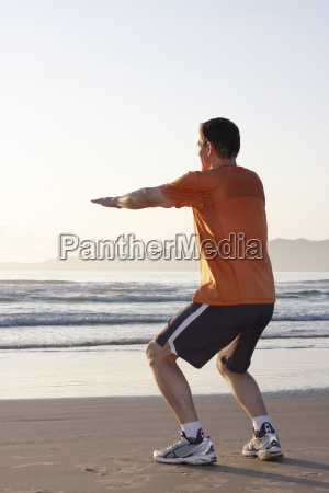 runner does squats on the beach