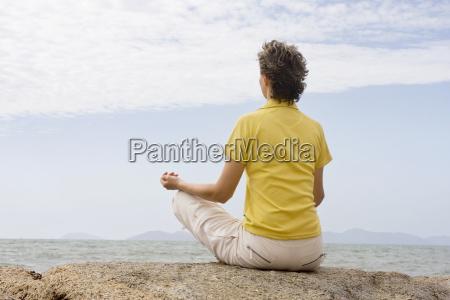 woman meditating on the sea