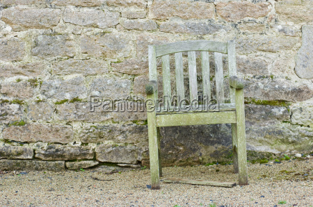 old chair in front of stone