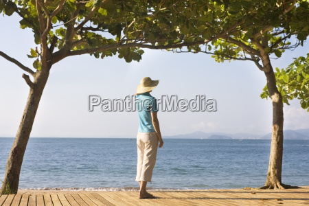 woman between trees on the beach