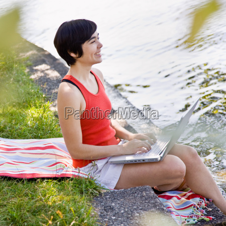 woman using laptop near pond