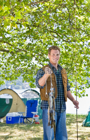 fisherman, carrying, fish, at, campsite - 2822959