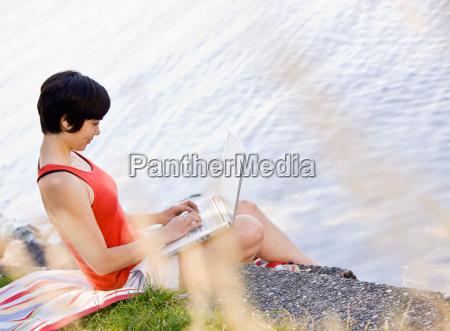 woman, using, laptop, near, pond - 2822771