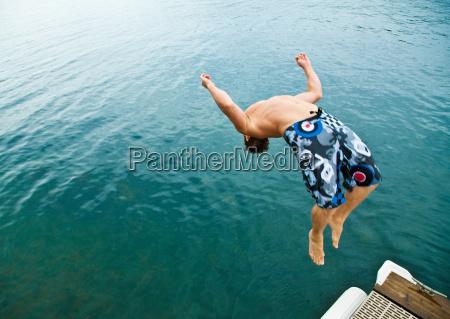 man doing back flip into lake