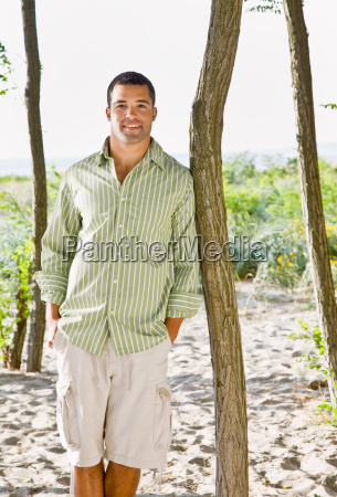 man leaning on tree at beach