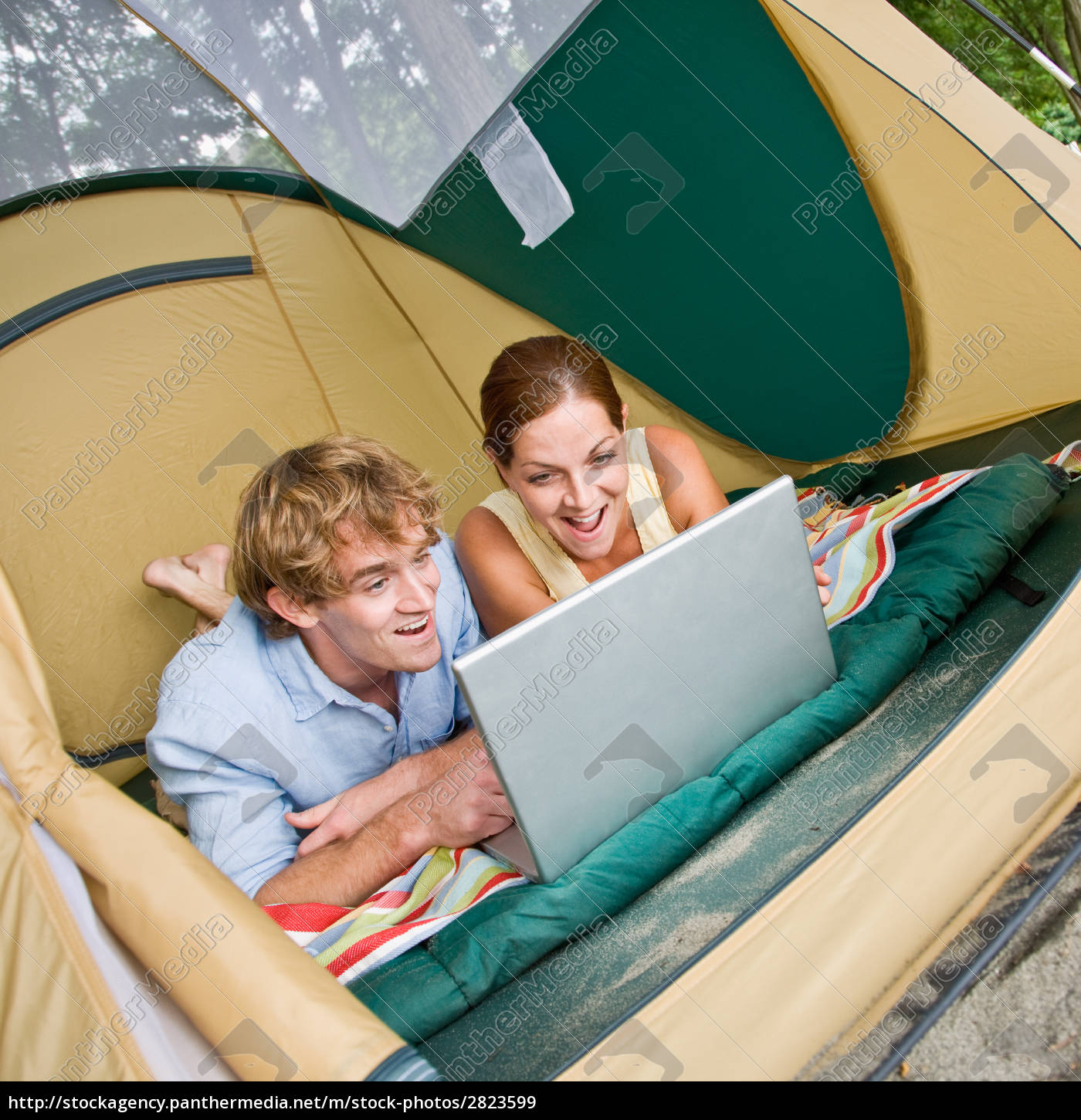 couple, laying, in, tent, using, laptop - 2823599