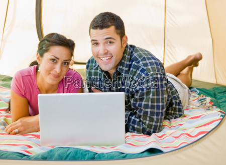 couple, laying, in, tent, using, laptop - 2823633