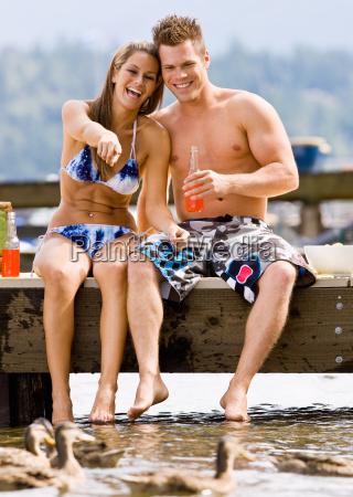 couple, sitting, on, pier, drinking, soda - 2823231