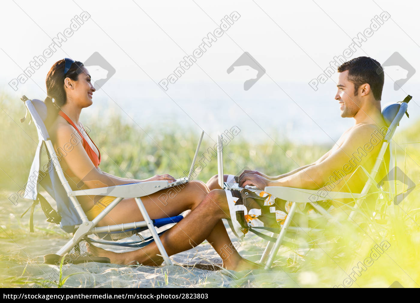 couple, using, laptops, at, beach - 2823803