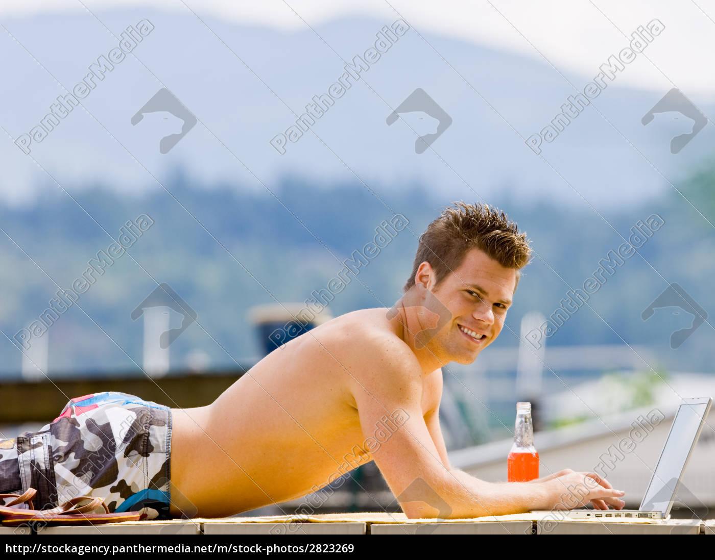 man, laying, on, pier, typing, on - 2823269
