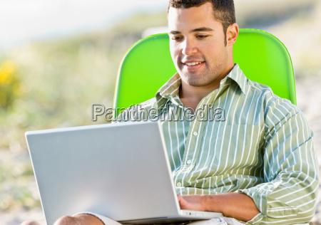 man, using, laptop, at, beach - 2823781