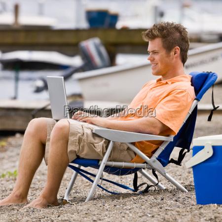 man, using, laptop, on, beach - 2823331