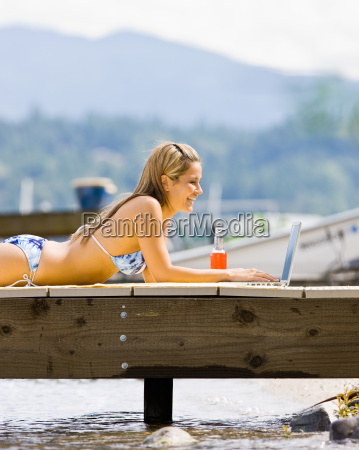 woman, laying, on, pier, typing, on - 2823291