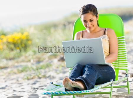 woman, using, laptop, at, beach - 2823793