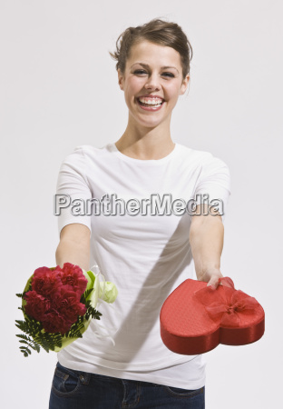 attractive young woman holding out roses