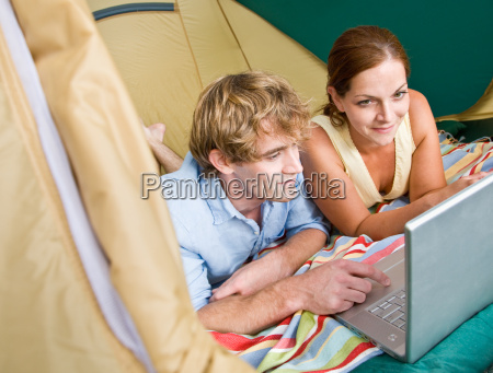 couple, laying, in, tent, using, laptop - 2824011