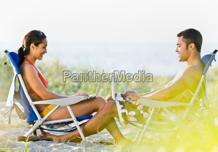 couple, using, laptops, at, beach - 2824007