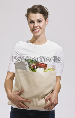 attractive brunette holding grocery bag