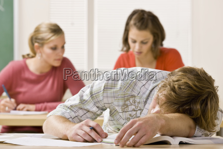 student, sleeping, at, desk, in, classroom - 2832263