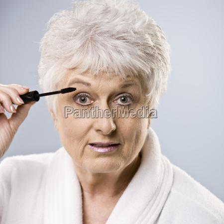 older woman putting on makeup