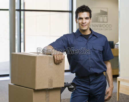 young man standing with boxes