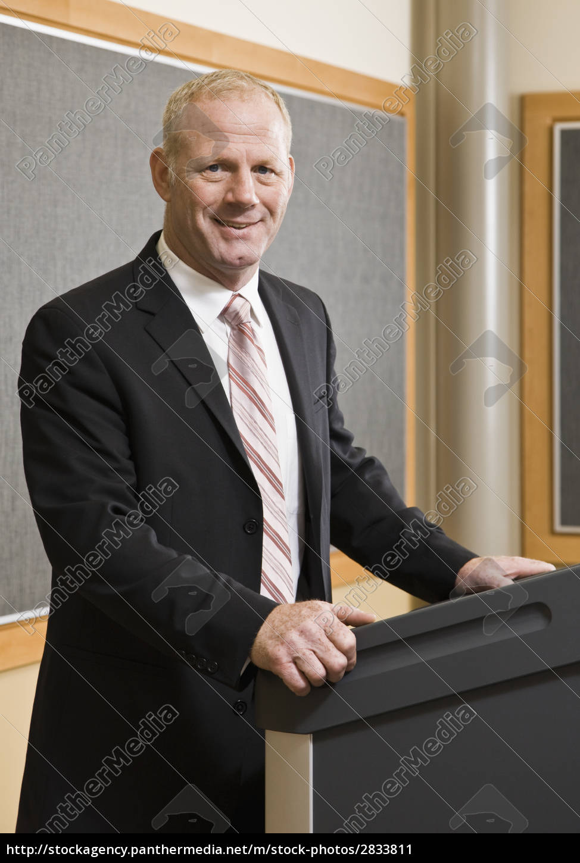 business, man, standing, at, podium, smiling - 2833811