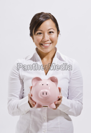 beautiful asian woman holding piggy bank