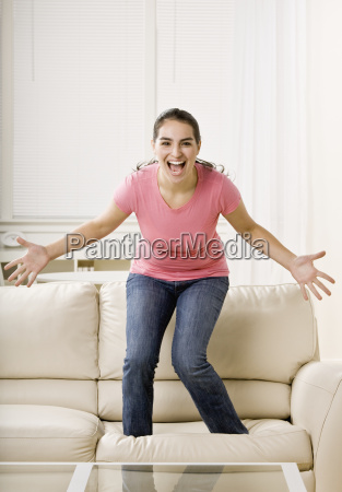 young, woman, standing, on, couch - 2834309