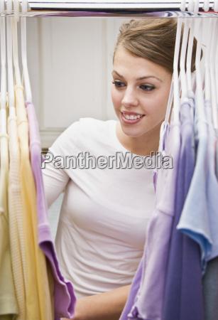 beautiful young woman looking through closet
