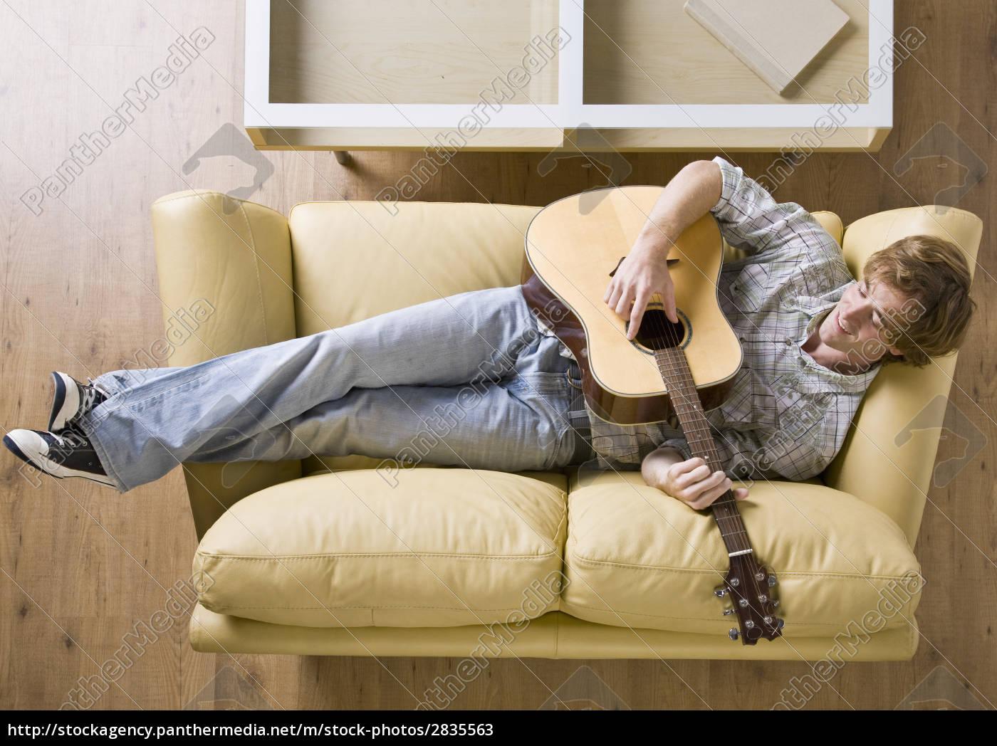 man, laying, on, sofa, playing, guitar - 2835563