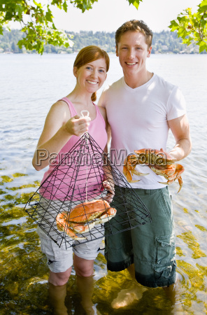 couple holding crab and trap