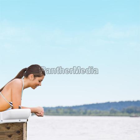 woman laying on pier at lake