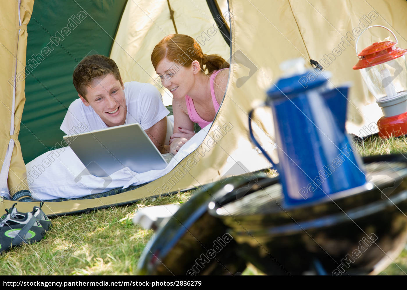 couple, laying, in, tent, with, laptop - 2836279