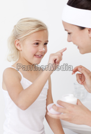 mother and daughter putting cream on