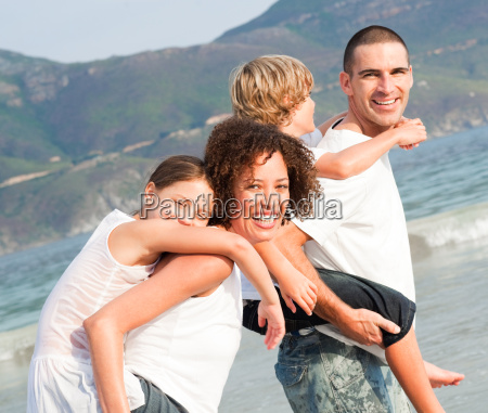 parents giving two young children piggyback