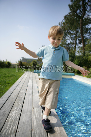 little boy walking beside a pool