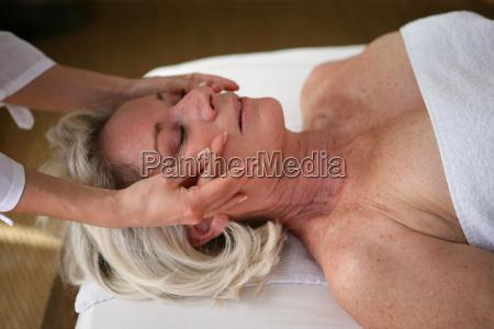 elderly woman being massaged face